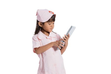 Asian little girl wearing a nurse uniform with hand holding a pad
