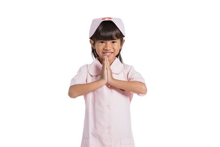 Asian little girl wearing a nurse uniform with both hands in front of the chest