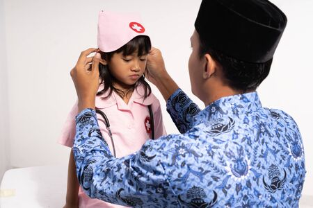Asian father wearing batik korpri dress his daughter in a doctors uniform