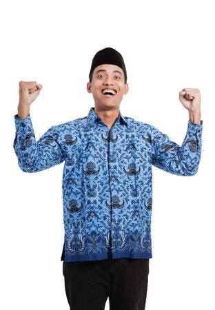 asian young man wearing batik korpri with spirited two hand gesture