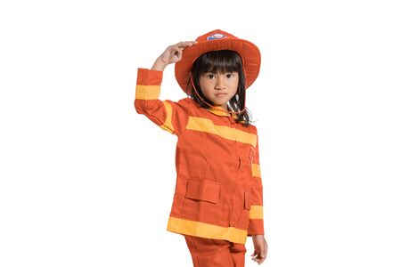 Little girl wearing a firefighter uniform with one hand holding a hat