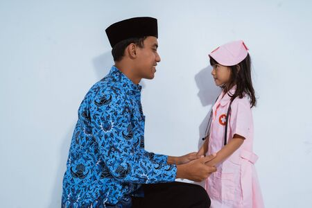 smiling father wearing batik korpri chatting with her daughter wearing doctor uniform Фото со стока
