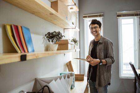 pose of smiling young asian entrepreneur when hold a clipboard Reklamní fotografie