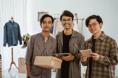 three young asian businessman posing looking at the camera when hold their working tool