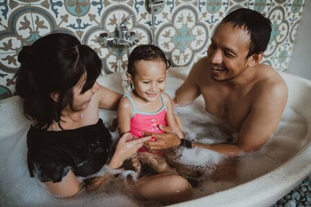 happy family with little daughter in bathtub