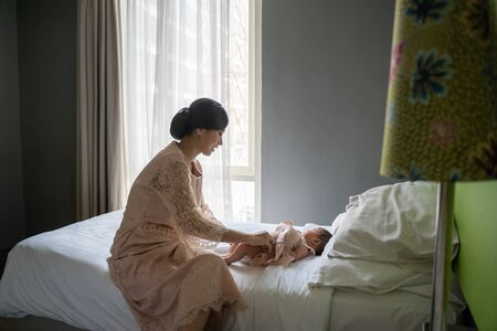Asian young mom wearing dress changes the babys diaper in the bedroom