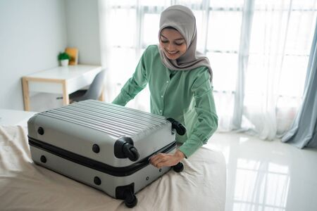Beautiful Muslim women tried to close her full suitcase Banque d'images