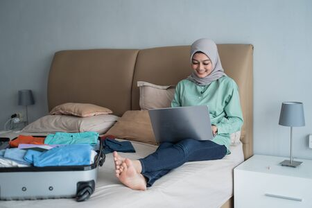 Asian muslim woman using laptop to looking departure schedules via online application