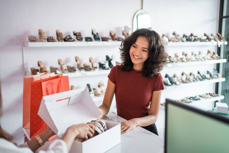 sale, shopping concept - young asian woman or shop assistant with shoe boxes at store