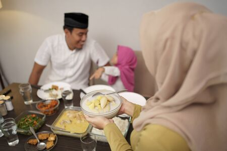 muslim mother serving some food for family