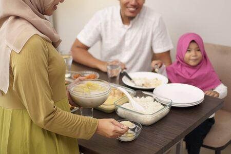 muslim mother serving some food for family dinner during ramadan kareem