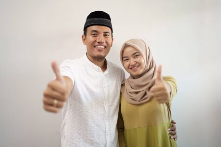 muslim couple showing thumb up over white wall Reklamní fotografie