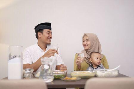 亚洲穆斯林家庭喝一杯水,在晚上打破快速