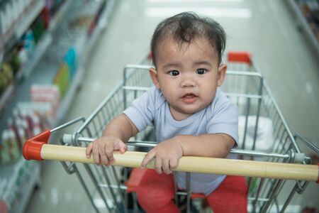happy infant baby sitting alone in shopping cart or trolley in grocery supermarket