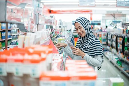 muslim asian woman shopping in grocery store supermarket buying some product