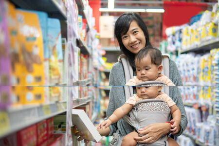 asian Mother and baby shopping in the supermarket. grocery store shopping