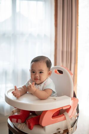 happy asian baby feeding time sitting on highchair