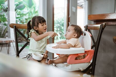 sibling feeding her little baby sister at home