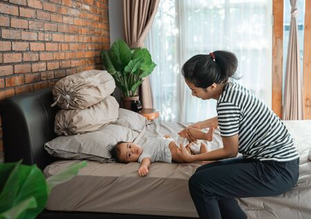 mother change her baby diaper on the bed
