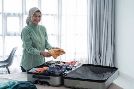 Muslim women wearing hijabs prepare clothes to be put in a suitcase