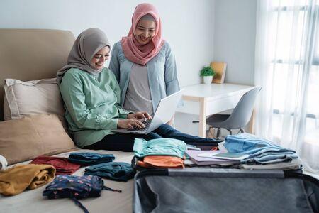 two muslim woman using laptop to looking departure schedules via online application 版權商用圖片