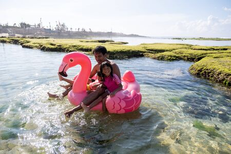 Asian father and two daughters ride flamingo buoy on the beach Banque d'images