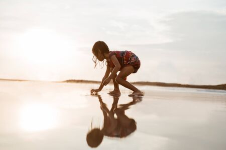 little girl bent over and playing sand when the waves came on the beach Stock Photo