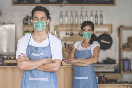 Kellnerin im Laden trägt Gesichtsmasken