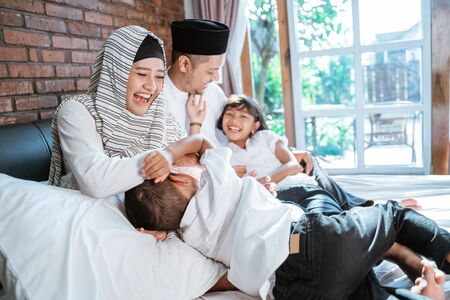 Muslim families with their children are relaxing and joking on the bed