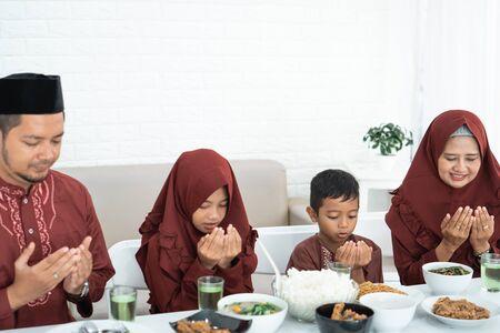 Muslim family pray when breaking fast Reklamní fotografie