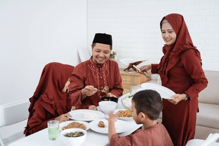 Muslim family sit to eat when breaking fast