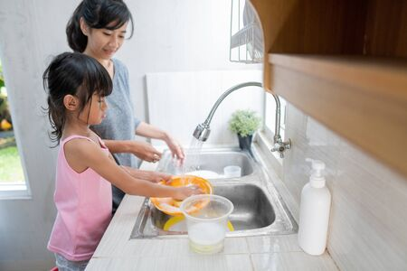 Daughter helping her mother in the kitchen