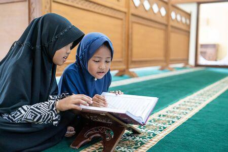 两个孩子读神圣的可兰经