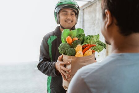 male courier delivering grocery to customer Stockfoto