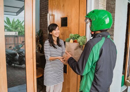 Smiling Woman Receiving Grocery Delivery At Home Stockfoto