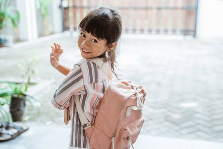 Kind winkt zum Abschied, bevor es zur Schule geht