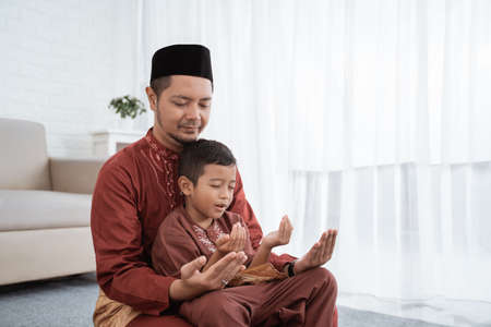 Father and son praying together Standard-Bild