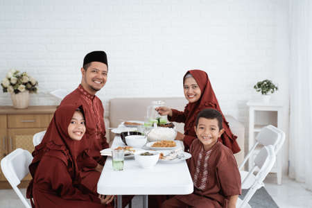 Muslim family sit and smile when looking at camera