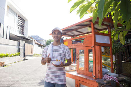 man selling bakso by walking and pushing down the food carts