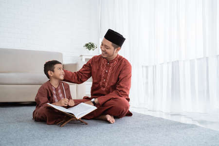 Son learns the Al-Quran with her father