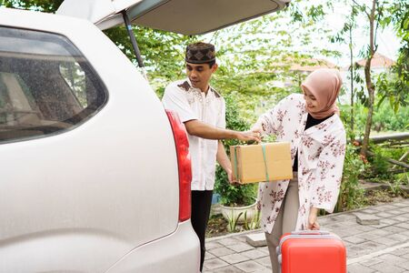 muslim couple packing suitcase in the car Stock Photo