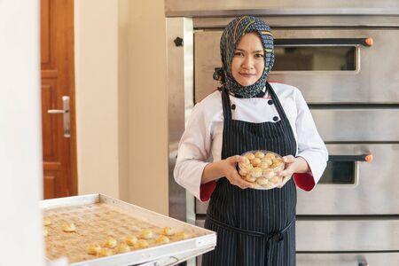 happy muslim woman baking pineapple tart Banque d'images