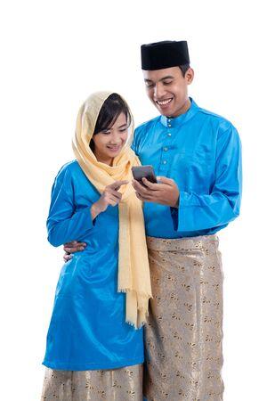 muslim couple using mobile phone