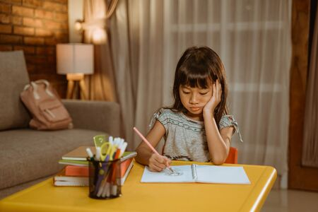 kid studying by herself in the evening