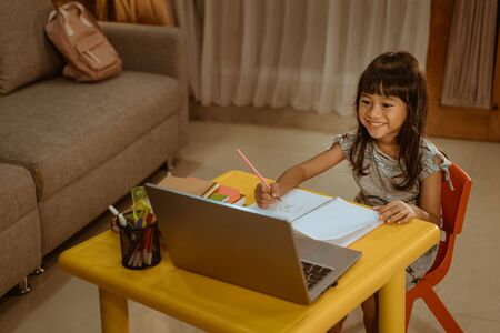 happy little girl doing homework using laptop 版權商用圖片