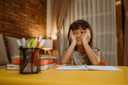kid feel bored while doing her homework