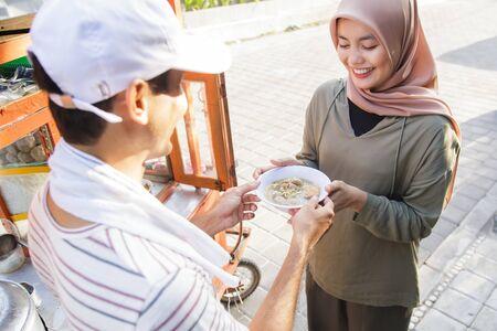 street food vendor handing a bowl of bakso