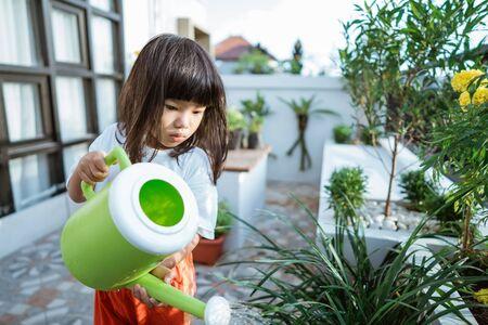 asian toddler gardening at home