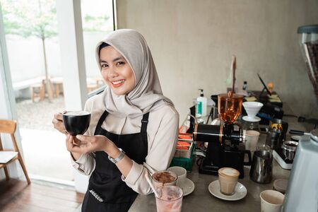 asian veiled waitress smiling hold a cup of coffee
