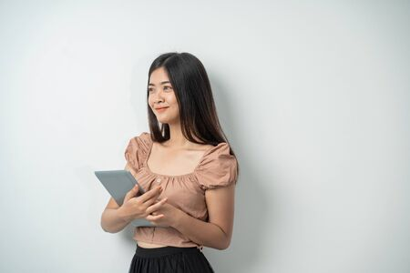 beautiful girl with long hair smiling while holding a tablet